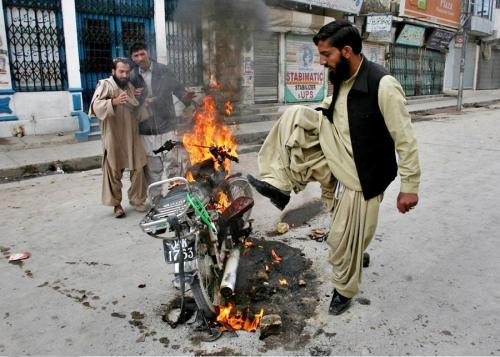 A non-Hazara burning a motorbike; proof of no Hazara hand behind burning the banks, vehicles and looting.